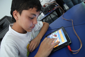 a young boy uses his tablet computer in class